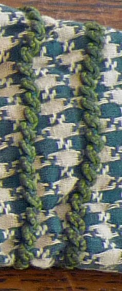 There are rows of trim on cuffs, shoulder caps, and bodice.