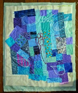 Stitched dragonfly and random satin-stitched shapes, free motion quilted.