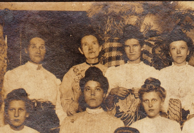 Look at the lady in the back row, second from left. Does the embroidery on her shoulder match that on the skirt of the lady with glasses, front row, far left?