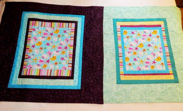 Two lap quilts featuring the same central fabric.