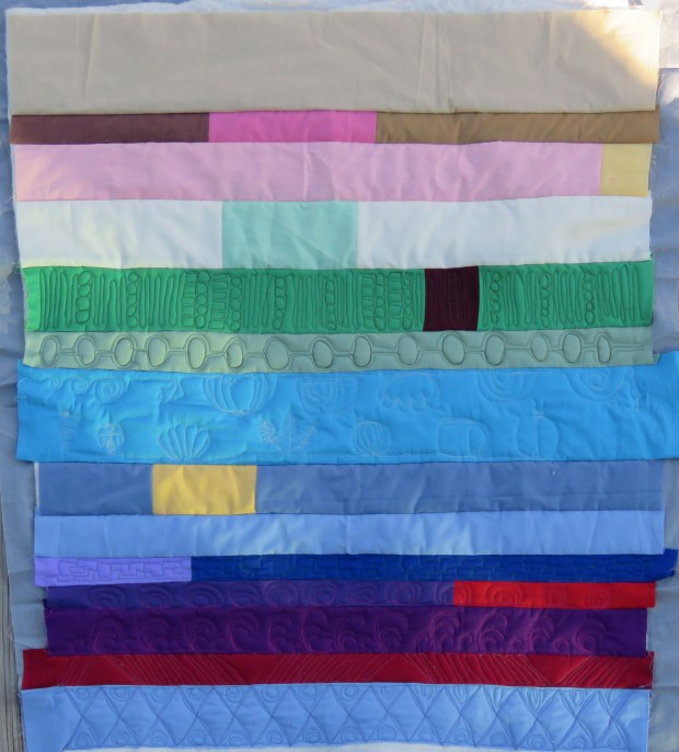 Strippy mini-quilt with about half the rows quilted.