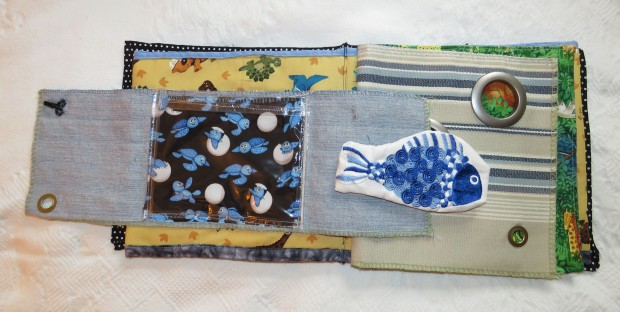 Sample page from the cloth book. The fish came from machine embroidered towel. I used some of those plastic curtain rings to make holes in one page, for peeking at animals on the next.