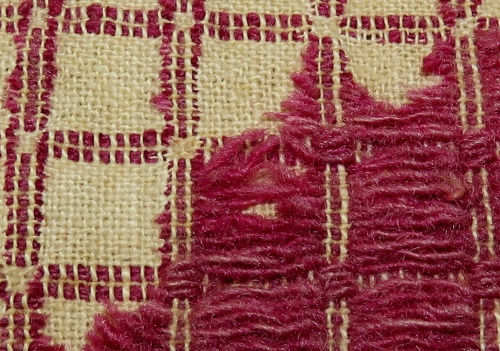 "This close-up shows why this weave structure is called ""overshot."" The red pattern threads are floating over the plain weave ground, tied down at intervals to keep them in place. But if you were to remove all of them, you would still have a viable cloth."