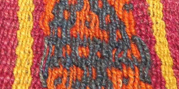 The orange and navy threads float along the surface, while the red and yellow threads intersect with the weft at shorter intervals.