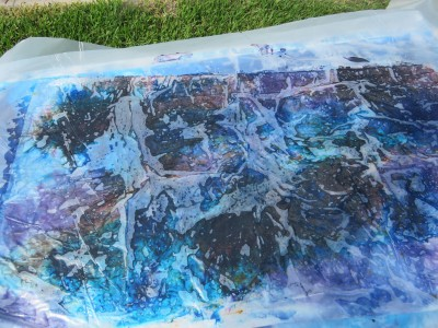 Plastic sheeting on top of dyed fabric.