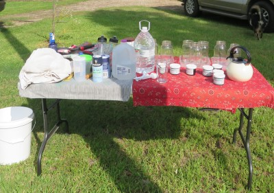 Supply table with dyes, jars, measuring spoons, water, etc.