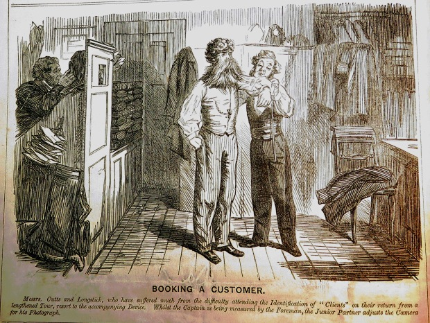 """Booking a Customer"" Messrs. Cutts & Longstick, who have suffered much from the difficulty attending the Identification of ""clients"" on their return from a lengthened Tour, resort to the accompanying Device. Whilst the Captain is being measured by the Foreman, the Junior Partner adjusts the Camera for his Photograph."