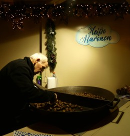 Man bagging up freshly roasted chestnuts.