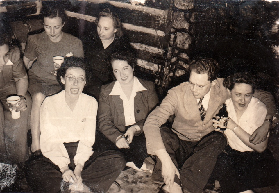 a group of people in a log cabin c. 1935