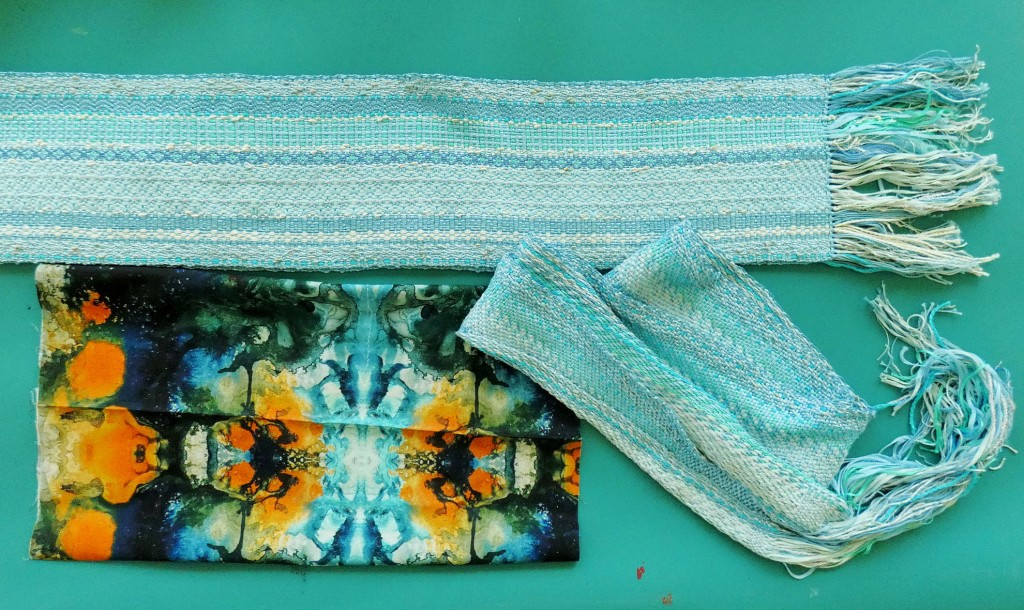 two handwoven scarves and one piece of printed fabric